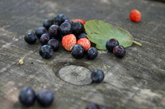 Blueberries and strawberries are pink. Near the green leaf on a wooden table Stock Photo
