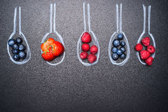 Blueberries, strawberries, raspberries, and a variety of berries, in painted chalk spoons, place  text, top view Royalty Free Stock Image