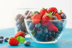 Blueberries and strawberry in glass bowl on wooden table background. Berries, summer fruit on wooden table. Healthy lifestyle concept, Strawberries, blueberries Stock Photography