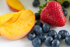Blueberries, strawberry and peach. Fruit assorty - healthy food background Royalty Free Stock Image