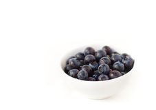 Blueberries in white bowl. A bowl full of fresh blueberries rests on a white background Stock Photos
