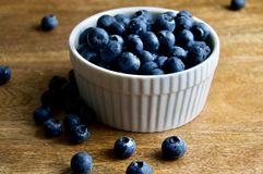 Blueberries in a white bowl. Fresh blueberries in a white bowl on a wood surface Stock Photography