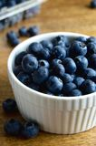 Blueberries in a white bowl. Fresh blueberries in a white bowl on a wood surface Stock Photo