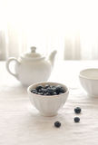 Blueberries in white bowl on table Stock Photo