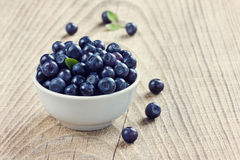 Blueberries in the white bowl on a wood rustic background Stock Photos