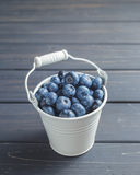 Blueberries in white bucket over black wooden background Stock Images