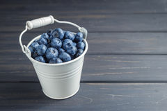 Blueberries in white bucket over black wooden background Royalty Free Stock Photo