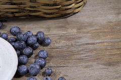 Blueberries and white cermaic plate on wooden background. A hand made ceramic plate with summertime blueberries on a rustic wooden background Royalty Free Stock Photography