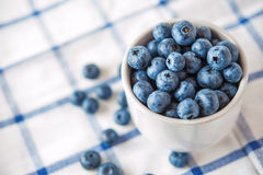 Blueberries in a white cup. Blue berries on checkered napkin Royalty Free Stock Photos