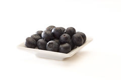 Blueberries on a white plate. Some blueberries on a white plate placed on a white background Royalty Free Stock Images