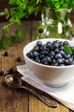 Blueberries in white plate on a wooden surface Royalty Free Stock Photos