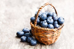 Blueberries   in wicker basket on rustic wooden background Royalty Free Stock Image