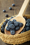 Blueberries in a wicker basket on a wooden spoon Stock Photos