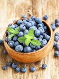 Blueberries in a Wooden Bowl with Mint Leaf Royalty Free Stock Photos