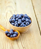Blueberries in wooden bowl and spoon on board Stock Photos