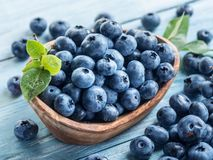 Blueberries in the wooden bowl on the table royalty free stock photography
