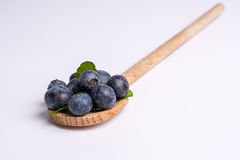 Blueberries on wooden spoon on white background Royalty Free Stock Photos