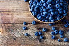Blueberries on wooden table. Blueberry bowl on vintage background with copyspace. Berries frame, healthy food concept.  Stock Photo