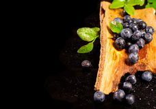 Blueberries in wooden tub on a black surface Royalty Free Stock Photography