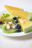 Blueberries, yellow watermelon and kiwifruit Royalty Free Stock Photography