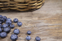 Blueberris on a wooden background. Nice summer time blueberries on a rustic wooden backroung and a wicker basket Stock Image
