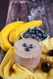 Blueberry banana cherry smoothie. Blueberry banana cherry yogurt smoothie on wooden background Royalty Free Stock Photo