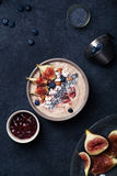 Blueberry banana smoothie bowl with figs and coconut. Dark food phorography concept. Flatlay with copy space. Vertical composition stock image
