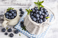 Blueberry basket and jug on white wooden table. White wicker basket and ceramic jug with fresh blueberries on blue checkered cloth over white painted grunge Stock Images