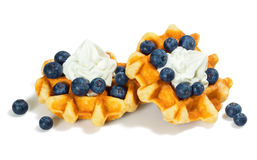 Blueberry Belgium Waffles with Whipped Cream. Two Liege style Belgian waffles on a white background with blueberries and whipped cream. Liege waffles are dense Stock Image