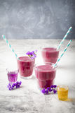 Blueberry, blackberry, honeysuckle, honeyberry smoothie with violet syrup and acai. Stock Images