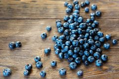 Blueberries background. Blueberries on vintage wooden table. Blueberry border design. Ripe and juicy fresh picked bilberries close up. Copyspace for your text Royalty Free Stock Image