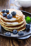 Blueberry buttermilk pancakes with maple syrup on rustic table. Blueberry buttermilk pancakes in cast iron pan served hot with maple syrup on rustic wooden table royalty free stock photos