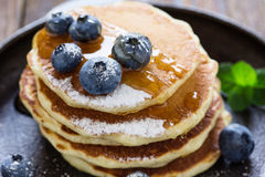 Blueberry buttermilk pancakes with maple syrup on rustic table. Blueberry buttermilk pancakes in cast iron pan served hot with maple syrup on rustic wooden table royalty free stock photography