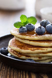 Blueberry buttermilk pancakes with maple syrup on rustic table. Blueberry buttermilk pancakes in cast iron pan served hot with maple syrup on rustic wooden table stock photography