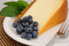 Blueberry and Cheese Cake. Seasonal blueberries with a slice of plain cheese cake with a mint leaf garnish served on a white saucer and a silver fork Stock Photos
