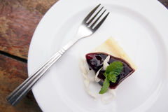 Blueberry Cheesecake. Blueberry cheese cake with fork on white dish Stock Photography