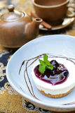 Blueberry cheesecake with cup of tea and kettle Royalty Free Stock Photo