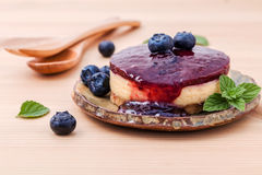 Blueberry cheesecake with fresh mint leaves on wooden background. Selective focus depth of field Stock Image