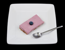 Blueberry cheesecake with a spoon on a white plate isolated on black Stock Photography