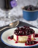 Blueberry Cheesecake at Tea Time. Blueberry cheesecake on vintage plate with lavender tea in the background Royalty Free Stock Images
