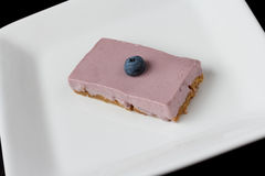 Blueberry cheesecake on a white plate isolated on black Stock Images