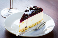 Blueberry cheesecake in white plate. On wood table Royalty Free Stock Images