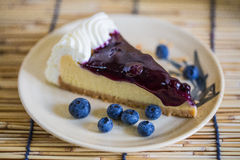 Blueberry cheesecake on the wooden background with  blueberries. A piece of blueberry cheesecake on the wooden background with blueberries Royalty Free Stock Image