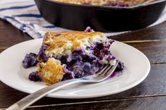 Blueberry Cobbler Baked in Cast Iron Skillet. Close up of slice of fresh baked blueberry cobbler sitting on white plate with fork royalty free stock photography