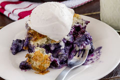 Blueberry Cobbler Baked in Cast Iron Skillet. Close up of slice of fresh baked blueberry cobbler sitting on white plate with fork topped with vanilla bean ice royalty free stock image