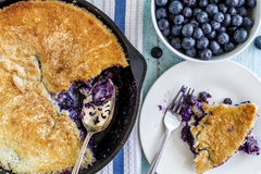 Blueberry Cobbler Baked in Cast Iron Skillet. Homemade fresh blueberry cobbler baked in cast iron skillet pan with piece on white plate and bowl of blueberries stock photos