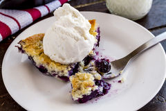 Blueberry Cobbler Baked in Cast Iron Skillet. Single slice of fresh baked blueberry cobbler on white plate with fork topped with vanilla bean ice cream and glass royalty free stock photo