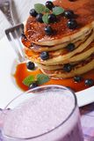 Blueberry cocktail and pancakes with berries and maple syrup Stock Photos