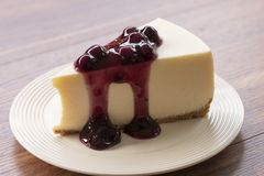 Blueberry cream cheesecake in white plate on wood table. A Blueberry cream cheesecake in white plate on wood table Stock Photos