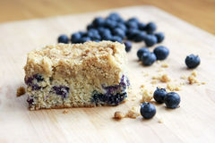 Blueberry Crumb Cake. A piece of blueberry crumb cake on a wooden cutting board royalty free stock photo